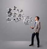 Handsome boy singing and listening to music with musical notes Royalty Free Stock Image