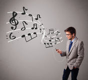 Handsome boy singing and listening to music with musical notes Stock Images