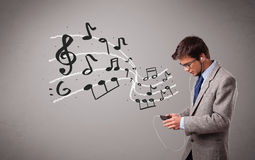Handsome boy singing and listening to music with musical notes Royalty Free Stock Photography