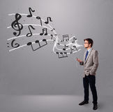 Handsome boy singing and listening to music with musical notes Stock Photo