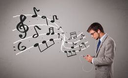 Handsome boy singing and listening to music with musical notes Stock Image