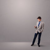 Handsome boy standing and holding a phone Stock Photo