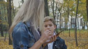 Missing sad boy near mother with phone. Handsome boy stands near his mother. Woman looks at the screen of her phone. Sad boy is missing and looks at the mother stock footage