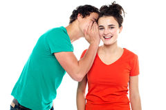 Handsome boy talking secret to young girl. In her ear, girl laughing over isolated white background stock photos