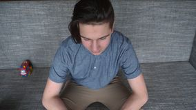 A handsome boy a teenager in desperation sits on a gray sofa. Brunette with long hair Royalty Free Stock Images