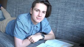 A handsome boy a teenager reads a book on a gray sofa, brown eyes. Brunet with long hair Stock Photos