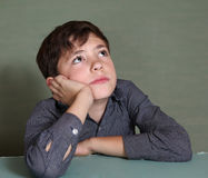 Handsome boy thinking on blue wall background Royalty Free Stock Images