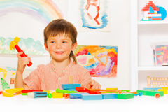 Handsome boy with toy hammer in the classroom Stock Images