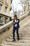 Guy walking down steps with newspaper. Handsome boy walking down steps with newspaper. Young man dressed in black suit looking at watch. Concept of businesslike Stock Photos