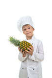 Handsome boy wearing chef uniform holding ananas. Handsome teen boy wearing chef uniform holding ananas. Portrait of a happy cute male child cook with fresh Stock Photos