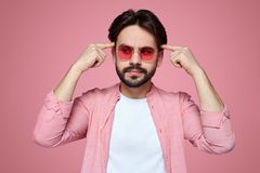 Handsome boy wearing stylish outfit and sunglasses looking away with thoughtful expression, keeping index fingers on his head. stock image