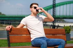 Handsome boy wearing sunglasses, sitting on a bench on a pier and drinking coffee to go. Taking a break from city rush. Background scenery bridge, river, pier Stock Images