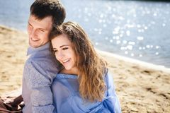 Handsome boyfriend and beautiful girlfriend resting outdoor. Young lovely couple resting on beach, handsome boyfriend and beautiful girlfriend smiling and Stock Photo