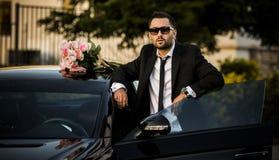 Handsome boyfriend in black suit waiting his girlfriend on street. Stock Photo
