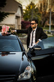 Handsome boyfriend in black suit waiting his girlfriend on street. Royalty Free Stock Image