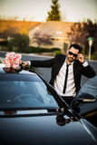 Handsome boyfriend in black suit waiting his girlfriend on street. Stock Photography