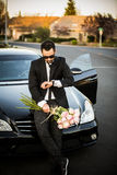 Handsome boyfriend in black suit waiting his girlfriend on street. Royalty Free Stock Photos