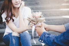 Handsome boyfriend is giving beautiful flower bouquet to his beautiful girlfriend. She gets surprised and smiles when she sees th stock photography