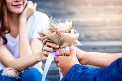 Handsome boyfriend is giving beautiful flower bouquet to his beautiful girlfriend. She gets surprised and smiles when she sees th stock images