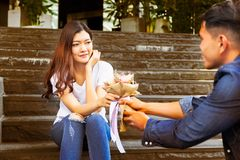 Handsome boyfriend is giving flower bouquet to girlfriend and he royalty free stock photo