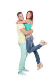 Handsome boyfriend lifting his girlfriend in his arms Stock Photography