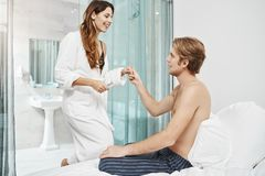 Handsome boyfriend with naked chest sitting on bed and inviting girlfriend to join him. Happy lovers just woke up and. Getting ready to go to beach while on Stock Photography
