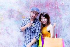 Handsome boyfriend is taking girlfriend to shopping mall. Handsome guy use credit card for buying favorite goods. Beautiful royalty free stock photo