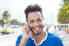 Handsome brazilian man at phone at city Royalty Free Stock Images