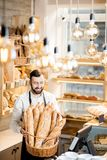 Seller in the bread store. Handsome bread seller with basket full of baguettes in the beautiful store with bakery products stock image