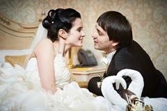 Handsome bride and groom in bedroom Stock Photos