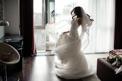 Handsome bride in white dress and veil dancing near the window. Handsome elegant brunette bride in white lacy wedding dress and veil dancing near the window Stock Image