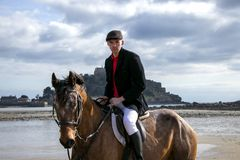 Good Looking  Male Horse Rider riding horse on beach in traditional riding clothing with St Michael`s Mount in background Royalty Free Stock Image