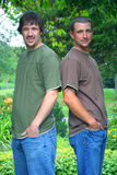 Handsome brothers. Handsome adult friends or brothers outside in a park with a nature green background Royalty Free Stock Photo