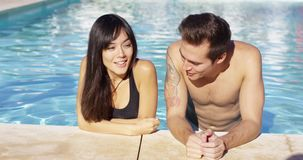 Handsome brown haired couple in blue pool stock video