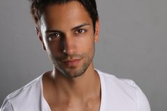 Handsome brown man model posing. On a gray background Stock Images