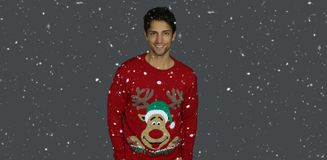 Handsome brown man wearing a Christmas sweater. On a gray background royalty free stock photos