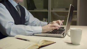 Handsome brunet man in suit and necktie typing on laptop computer at desk. In office handsome brunet man in suit and necktie typing on laptop computer at desk stock video footage