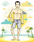 Handsome brunet young man standing on tropical beach in shorts. Royalty Free Stock Photography