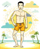 Handsome brunet young man standing on tropical beach in shorts. Royalty Free Stock Images
