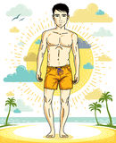 Handsome brunet young man standing on tropical beach in shorts. Royalty Free Stock Image