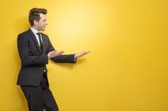 Handsome brunette businessman indicates something Stock Photography