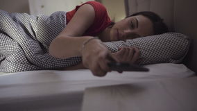 Handsome brunette girl is wakes up in a bed and starts to use her mobile device. stock video