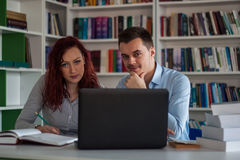 Handsome brunette guy and beautiful redhead student girl serious. Ly discussing, studying and learning together while working on the project in the library with Stock Photography
