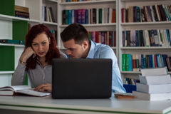 Handsome brunette guy and beautiful redhead student girl serious. Ly discussing, studying and learning together while working on the project in the library with Royalty Free Stock Photos
