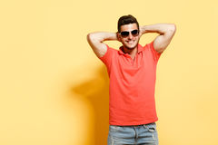 Handsome brunette guy holding hands behind head. Handsome brunette guy in sunglasses holding hands behind head smiling wearing red shirt standing against yellow Royalty Free Stock Photo