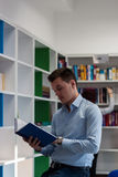 Handsome brunette guy looking away and standing next to the book. Shelf with a book in his hands wide opened and pencil in his hand. Redhead girl in the Royalty Free Stock Photography