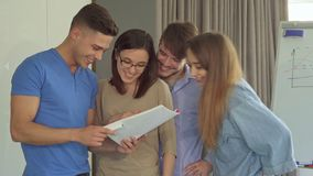 Guy shows his coworkers something funny in his journal. Handsome brunette guy showing his coworkers something funny in his journal. Young people laughing from royalty free stock image