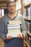 Handsome brunette librarian posing in library holding a pile of books Royalty Free Stock Photography