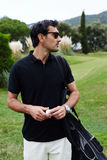 Handsome brunette man in glasses with golf bag on shoulder holding ball in the hands Royalty Free Stock Photo