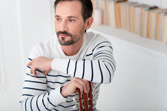 Handsome brunette man leaning on a musical instrument Stock Photography